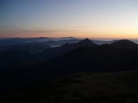 První ranní paprsky světla z Velkého Kriváňa. Uprostřed se tyčí Veľký a Malý Rozsutec, v pozadí za nimi Babí hora.